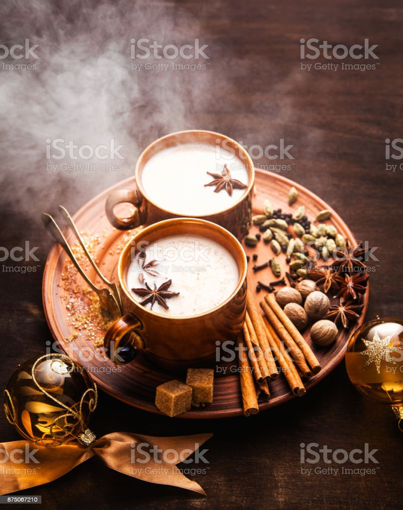 reeky Masala tea chai latte traditional hot Indian teatime ceremony sweet milk with spices, herbs organic infusion healthy beverage in porcelain cup on wooden table background. Christmas style. New Year's decorations stock photo
