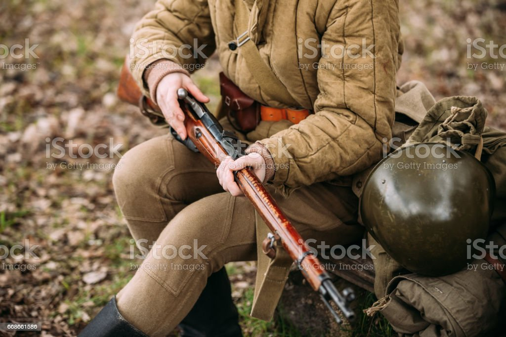 Re-enactor Dressed As Russian Soviet Infantry Soldier Of World War II Reloadng Rifle In Forest stock photo