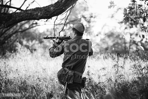 1143756392 istock photo Re-enactor Dressed As Soviet Red Army Soldier Aiming a Sub-machine Gun at Enemy. WWII WW2 Russian Intelligence Area. Photo In Black And White Colors 1143747477