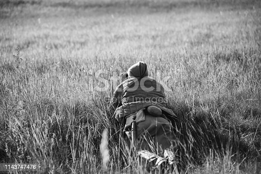 1143756392 istock photo Re-enactor Dressed As Soviet Red Army Soldier Scout Looks At An Old Army Binoculars. WWII WW2 Russian Intelligence Area. Photo In Black And White Colors 1143747476