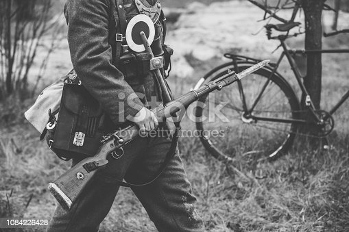 1061204700 istock photo Re-enactor Dressed As World War II German Soldier Feldgendarm Holding Rifle. Photo In Black And White Colors. Soldier Holding Weapon. German Military Ammunition Of A German WW2 Soldier 1084226428