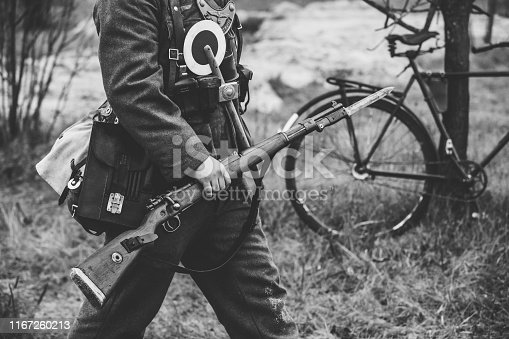 1061204700 istock photo Re-enactor Dressed As World War II German Soldier Feldgendarm Holding Rifle. Photo In Black And White Colors. Soldier Holding Weapon. German Military Ammunition Of A German WW2 Soldier 1167260213
