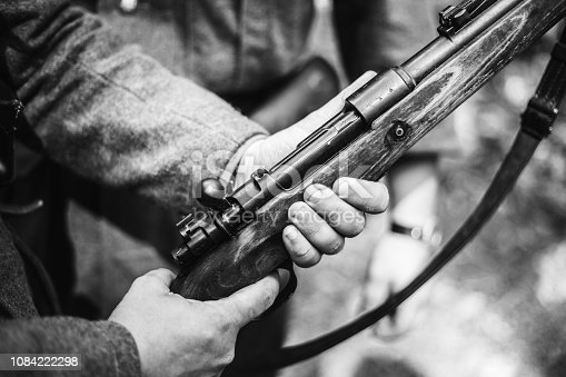 1061204700 istock photo Re-enactor Dressed As World War II German Soldier Holding Rifle. Photo In Black And White Colors. Soldier Holding Weapon. German Military Ammunition Of A German WW2 Soldier 1084222298