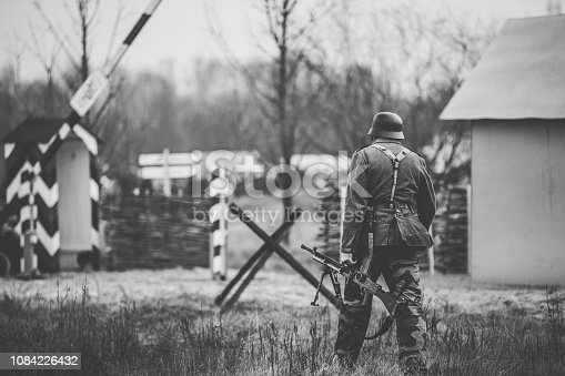 1061204700 istock photo Re-enactor Dressed As World War II German Soldier Holding Zb-30 Light Machine Gun. Soldier Holding Weapon. German Military Ammunition Of A German WW2 Soldier.  Photo In Black And White Colors 1084226432