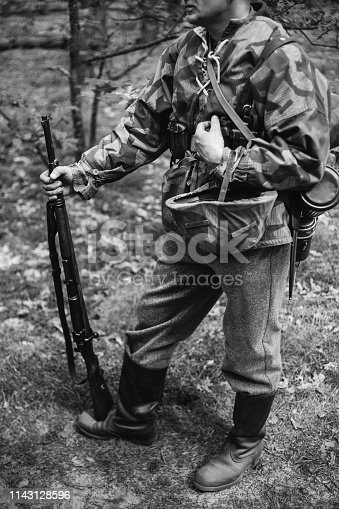 1061204700 istock photo Re-enactor Dressed As World War II German Wehrmacht Soldier Holds Rifle. Photo In Black And White Colors 1143128596
