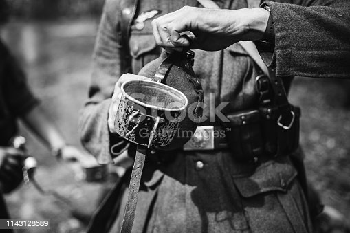 1061204700 istock photo Re-enactor Dressed As World War II German Wehrmacht Soldier Holds Flask With Water. Photo In Black And White Colors. Military German Soldier In Uniform Of WWII Times 1143128589