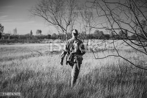 1143756392 istock photo Re-enactor Dressed As World War II Russian Soviet Red Army Officer Soldier Walking Through Autumn Meadow. Photo In Black And White Colors. Soldier Of WWII WW2 Times 1143747472
