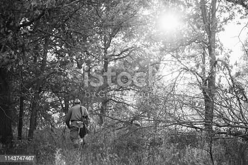 1143756392 istock photo Re-enactor Dressed As World War II Russian Soviet Red Army Soldier Walking With Weapon Through Autumn Forest. Soldier Of WWII WW2 Times 1143747467