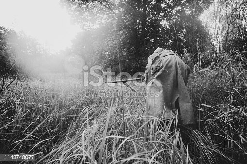 1143756392 istock photo Re-enactor Dressed As World War II Russian Soviet Red Army Soldier Fast Running With Rifle Weapon Through Autumn Forest. Soldier Of WWII WW2 Times. Photo In Black And White Colors 1143748077