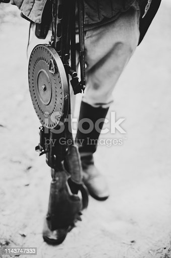 1143756392 istock photo Re-enactor Dressed As World War II Soviet Russian Red Army Soldier Holding World War II Weapon Degtyaryov DP Machine Gun. WWII WW2 Russian Ammunition. Photo In Black And White Colors. 1143747333