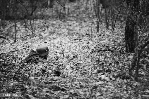 1143756392 istock photo Re-enactor Dressed In Overcoat As German Wehrmacht Infantry Soldier In World War II Hidden In Ambush In Autumn Forest. Photo In Black And White Colors. Soldier Of WWII WW2 1143128476