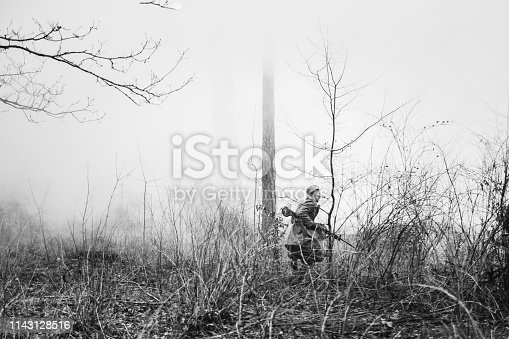 1143756392 istock photo Re-enactor Dressed In Overcoat As World War II Russian Soviet Red Army Soldier Running In Fog Smoke With Machine Gun In Misty Forest Ground. Photo In Black And White Colors. Soldier Of WWII WW2 1143128516