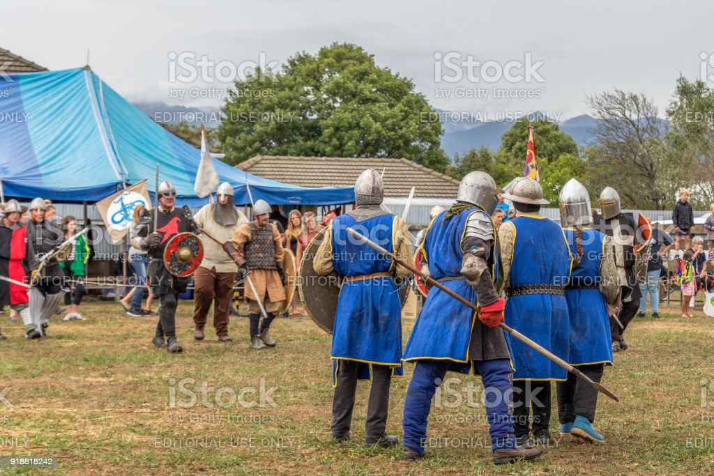 Reenactors battle in authentic armour at a medieval market in Levin...