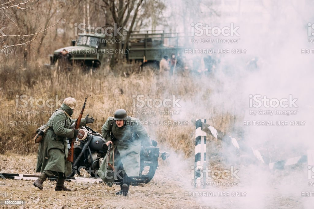 Re-enactors Dressed As German Wehrmacht Soldiers In Ww Ii Are Running On Battlefield. Celebration Of 73rd Anniversary Of Liberation Of Gomel From Nazi Invaders stock photo