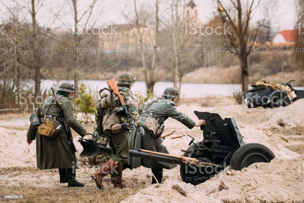 Re-enactors Dressed As German Wehrmacht Soldiers In WWII Roll Out Cannon At Firing Position.celebration Of 73rd Anniversary Of Liberation Of Gomel From Nazi Invaders stock photo
