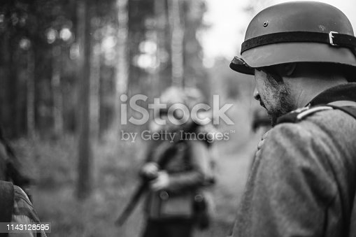 1143756392 istock photo Re-enactors Dressed As World War II German Wehrmacht Soldiers Marching Walking Along Forest Road In Summer Day. Photo In Black And White Colors. Military German Soldier Of WWII Times 1143128595