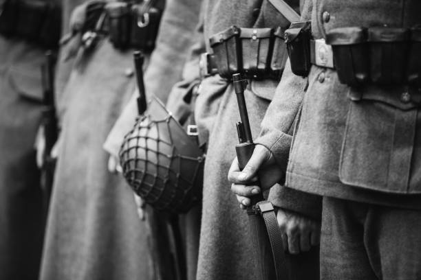 Re-enactors Dressed As World War II German Wehrmacht, Soldiers Standing Order With Rifle Weapons In Hands. Photo In Black And White Colors. Soldiers Holding Weapon Rifles stock photo
