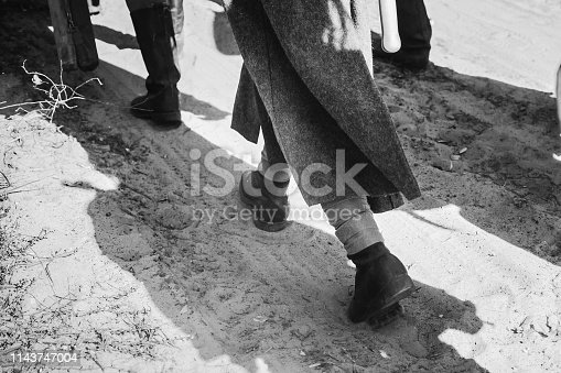 1143756392 istock photo Re-enactors Dressed As World War II Russian Soviet Red Army Soldiers Goes Along Road. Photo In Black And White Colors. Soldier Of WWII WW2 Times 1143747004