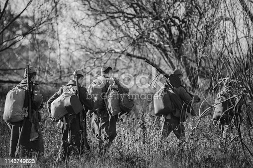 1143756392 istock photo Re-enactors Dressed As World War II Russian Soviet Red Army Soldiers Marching Through Forest In Autumn Day. Photo In Black And White Colors. Soldier Of WWII WW2 Times 1143749623