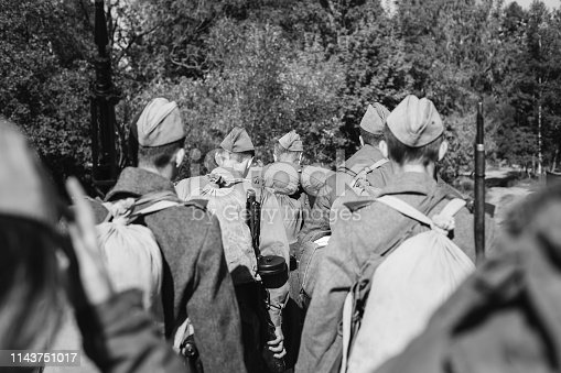 1143756392 istock photo Re-enactors Dressed As World War II Russian Soviet Red Army Soldiers Marching Through Forest In Autumn Day. Photo In Black And White Colors. Soldier Of WWII WW2 Times 1143751017