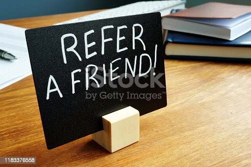 istock Refer a friend concept plate on the desk. 1183376558