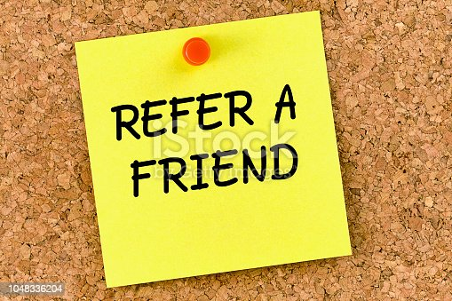 istock Refer a friend PostIt Note Pinned To Cork Board or corkboard 1048336204
