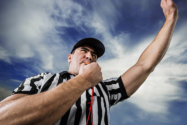 Referee against the clouds. Football referee blowing whistle.    referee stock pictures, royalty-free photos & images