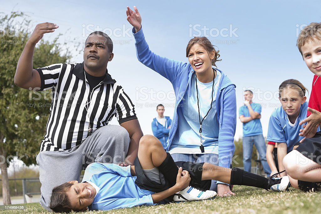 Referee and kids' soccer coach signaling help for injured player royalty-free stock photo