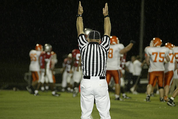 Referee at a Rain Football game Football game Referee (players in background) safety american football player stock pictures, royalty-free photos & images