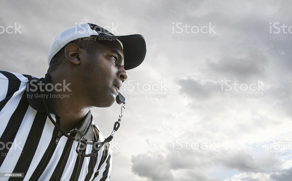 Referee Blowing Whistle During Football Game stock photo