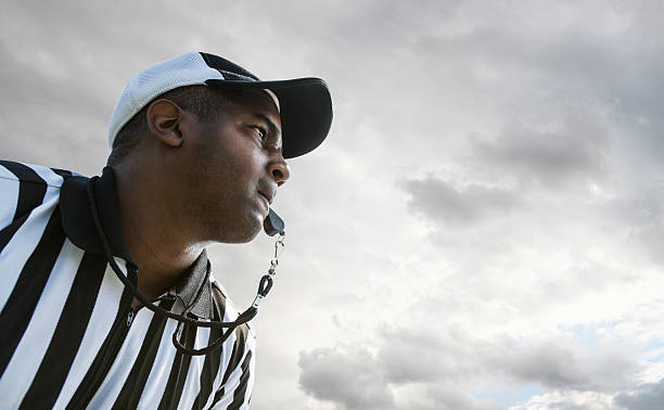 Referee Blowing Whistle During Football Game Referee Blowing Whistle During Football Game referee stock pictures, royalty-free photos & images