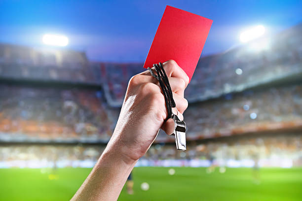 Referee holding up a red card and whistle inside a stadium Hand of referee with red card and whistle in the soccer stadium. referee stock pictures, royalty-free photos & images