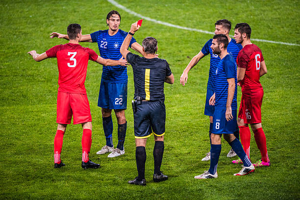 Referee holds up red card Referee holds up red card during football match, players arguing with referee. referee stock pictures, royalty-free photos & images