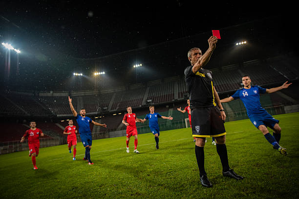 Referee holds up red card - Photo