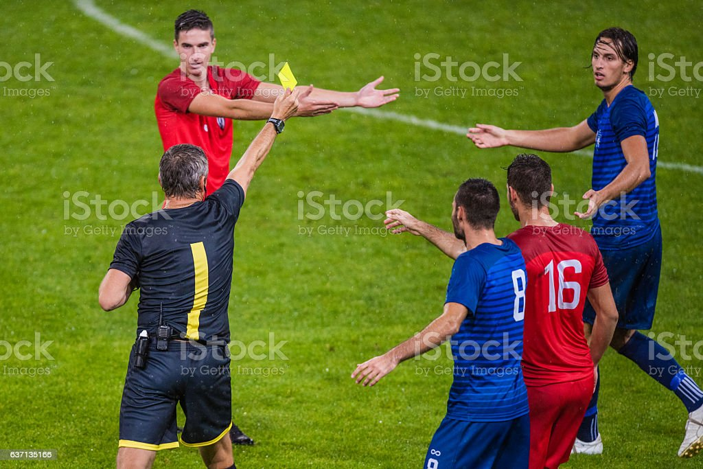 Referee holds up yellow card - Photo