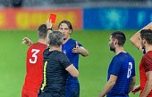 Referee showing red card during football match.