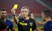Referee showing yellow card during football match.