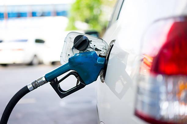 recarga combustible un un coche en gasolinera - echar combustible fotografías e imágenes de stock