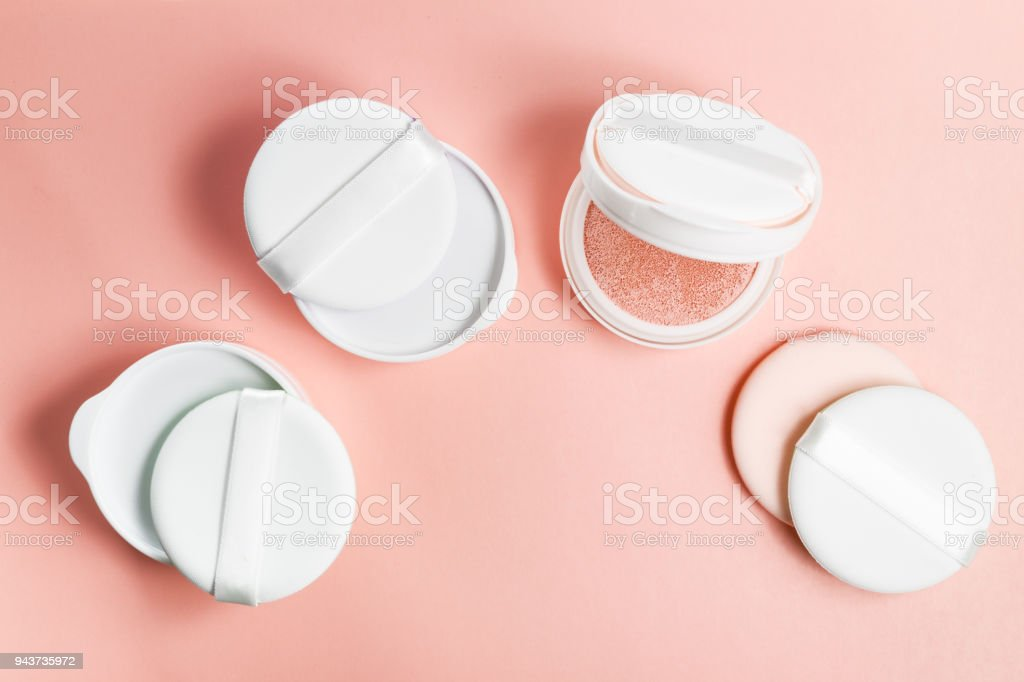 Refills of foundation and highlighter cushion on a pink background stock photo