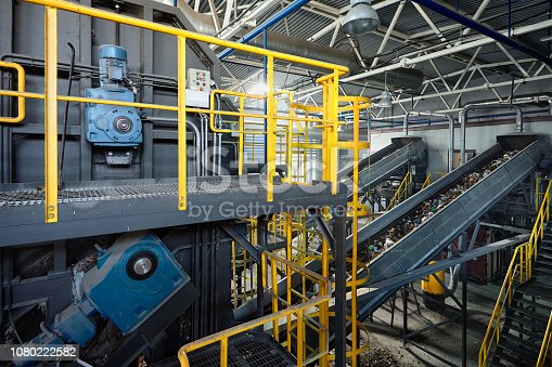 Refiner and chain-stepped conveyor equipment of modern waste recycling plant transports waste from receiving department to sorting, recycling and disposal.