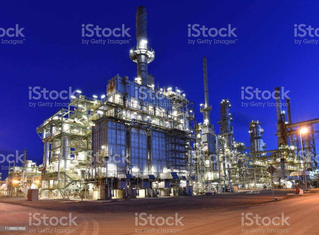 refinery - chemical factory at night with buildings, pipelines and...