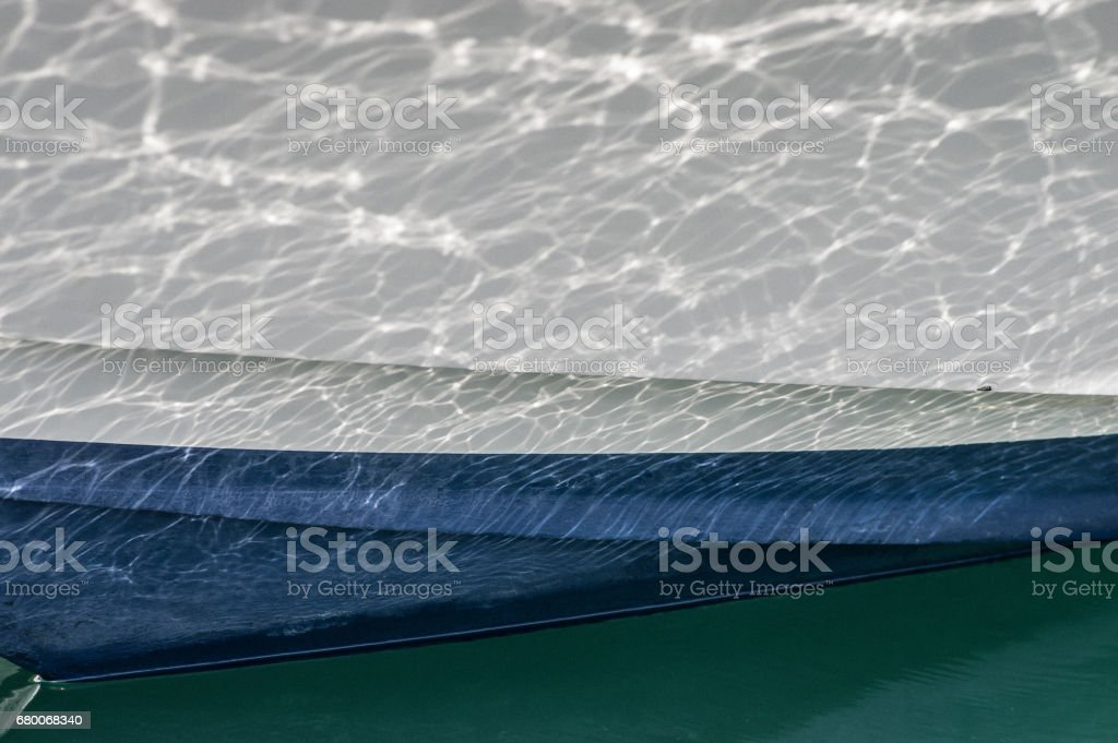 Reflected light caught in motion on the hull of a boat stock photo