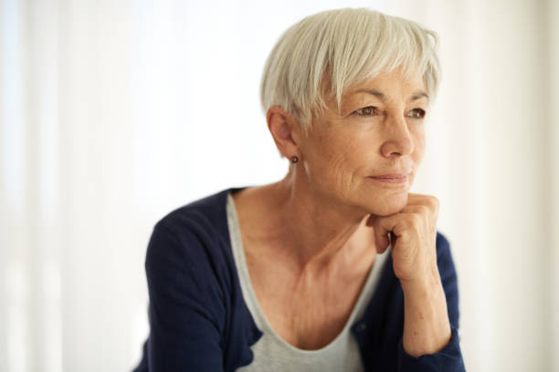 Reflecting on life's experiences Shot of a senior woman looking thoughtful at home introspection stock pictures, royalty-free photos & images