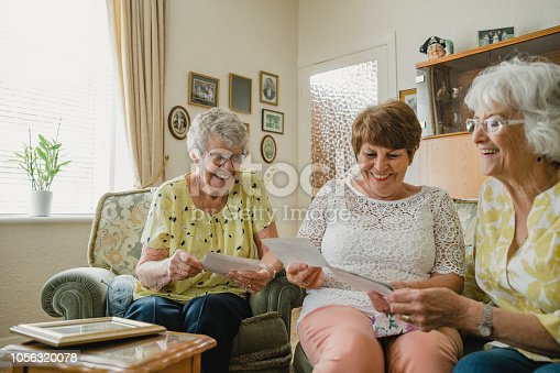 Three senior women are sitting at home together looking at old photographs and photo albums.