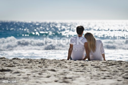 A young couple sitting together on the beach and admiring the beautiful view