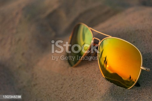 Reflecting sunglasses close up on beach sand with sunset and people reflection. Mirrored sunglasses on sandy beach in summer evening. Sunglasses on sand in sundown as summer vacation concept.