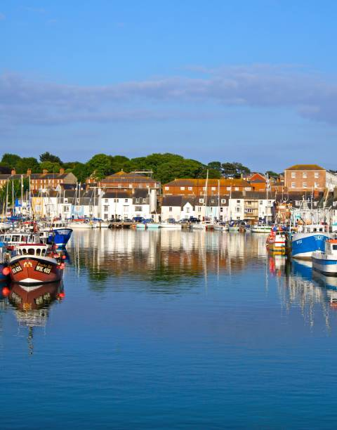 reflection across water weymouth dorset - weymouth stock photos and pictures