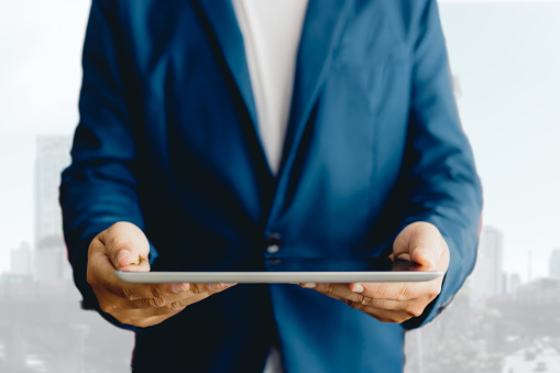 1025744818 istock photo Reflection Businessman using tablet analyzing data and economic growth graph chart  and copy space. Concept on tablet with hologram. 1148648346