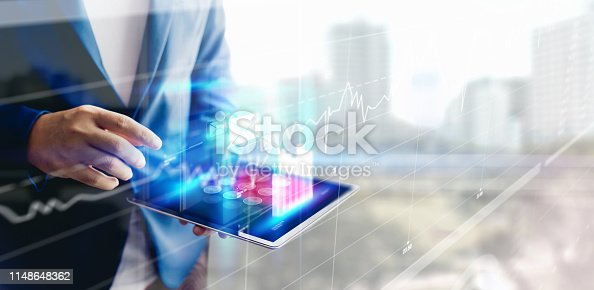 1051659174istockphoto Reflection Businessman using tablet analyzing data and economic growth graph chart. Concept on tablet with hologram. 1148648362