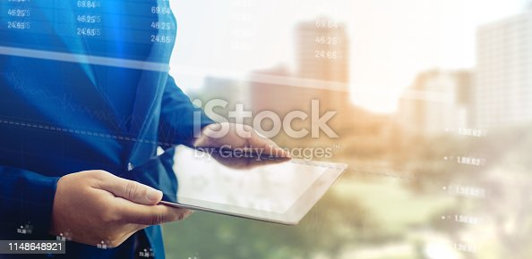 1051659174istockphoto Reflection Businessman using tablet analyzing data and economic growth graph chart. Concept on tablet with hologram. 1148648921
